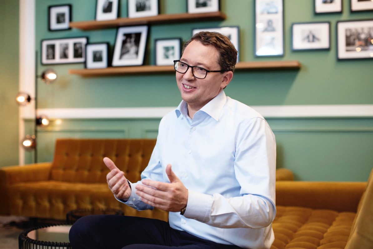 Pressefoto von Rainer Beaujean auf braunen Sitzmöbeln vor einer grünen Wand